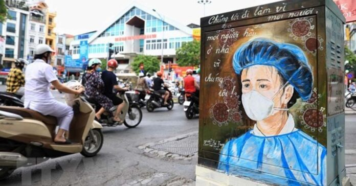 Scene from Vietnam depicting frontline medical worker, calling on people to stay at home (Photo: VNA)